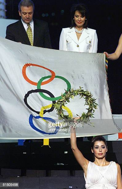Greek priestess holds a laurel wreath in front of the Olympic flag as Athens mayor Dimitris Avramopoulos and the president of the Athens Olympic...