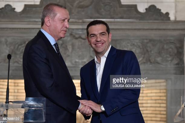 Greek Prime Minister Alexis Tsipras and Turkish President Recep Tayyip Erdogan shake hands after delivering a joint press conference in Athens on...