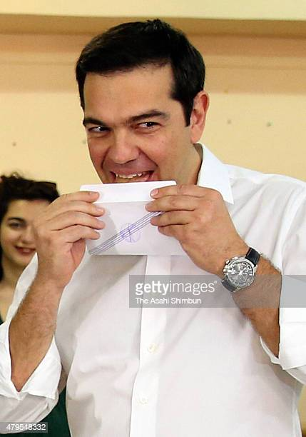 Greek Prime Minister Alexis Tsipras licks the envelope of his referendum vote before putting it in the ballot box at a school in the suburbs of...