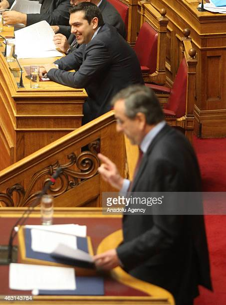Greek Prime Minister Alexis Tsipras listens as Greece's former Prime Minister Antonis Samaras speaks during a parliament session before the...