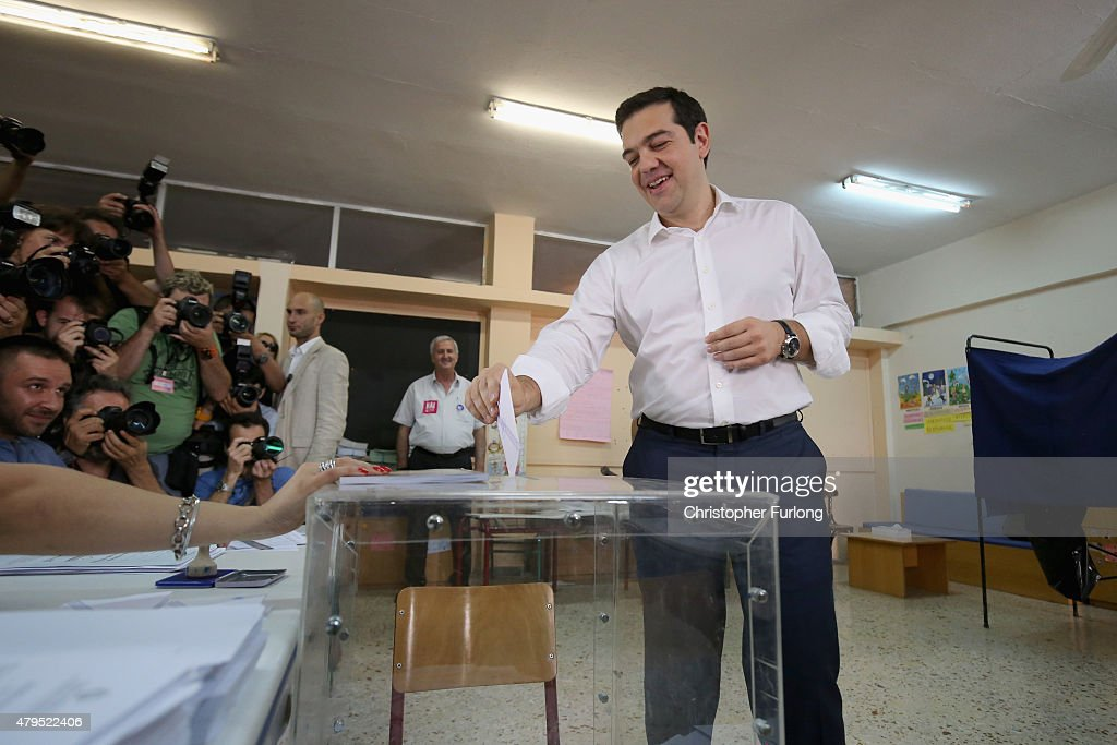 Greek Prime Minister Alexis Tsipras puts his referendum vote in the ballot box at a school in the suburbs of Athens on July 5 2015 in Athens Greece...