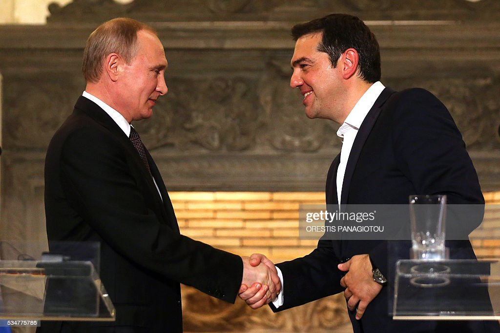 Greek Prime Minister Alexis Tsipras (R) shakes hands with President of the Russian Federation Vladimir Putin druing a joint press conference after their meeting in Athens on May 27, 2016. The visit -- Putin's first to the EU since December -- comes as the bloc's leaders are to discuss next month whether to renew sanctions on Russia's banking, defence and energy sectors that expire in July. / AFP / POOL / ORESTIS