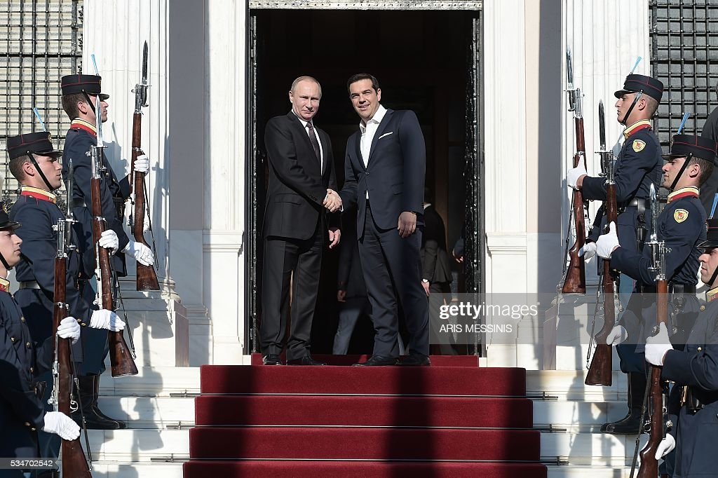 Greek Prime Minister Alexis Tsipras (R) shakes hands with Russia's President Vladimir Poutin before their meeting in Athens on May 27, 2016. The visit -- Putin's first to the EU since December -- comes as the bloc's leaders are to discuss next month whether to renew sanctions on Russia's banking, defence and energy sectors that expire in July. / AFP / ARIS