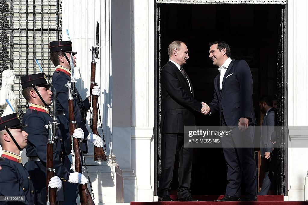 Greek Prime Minister Alexis Tsipras (R) shakes hands with Russia's President Vladimir Poutin before their meeting in Athens on May 27, 2016. Poutin is in Greece on a two-day working visit. / AFP / ARIS