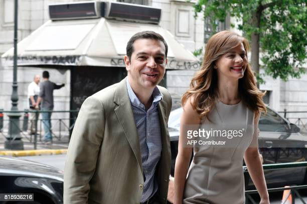 Greek prime minister Alexis Tsipras smiles while he arrives for his meeting with Greek Labour Minister Efi Achtsioglou at the labour ministry in...