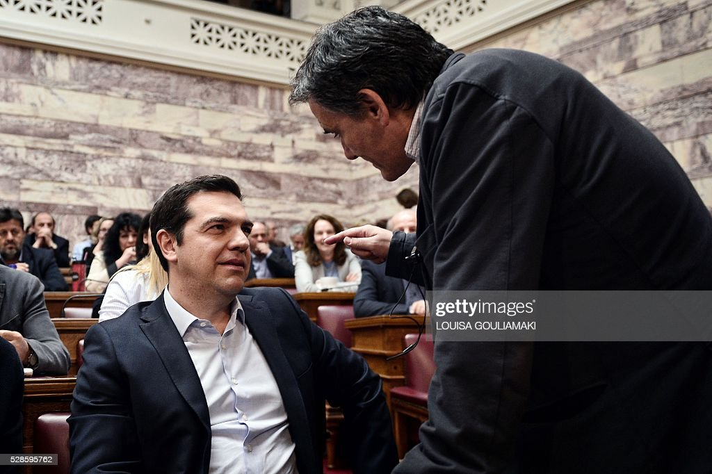 Greek Prime minister Alexis Tsipras (L) talks with Greek Finance minister Euclid Tsakalotos during the Syriza party's parliamentary group at the Greek parliament in Athens on May 6, 2016. Greece's main labour unions staged a 48-hour strike to protest controversial government plans to overhaul pensions and increase taxes, as demanded by international creditors. The announcement on May 5, 2016 of a general strike came after Greece's parliament said the government's pension and taxation reform bills would be debated and voted on this weekend. / AFP / LOUISA