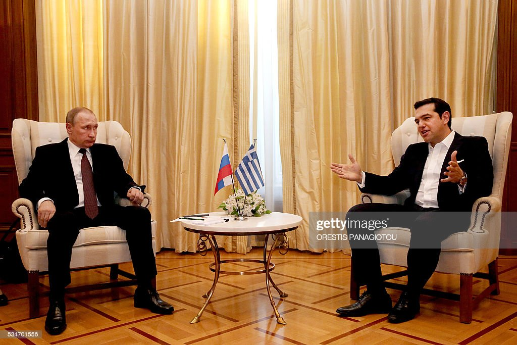 Greek Prime Minister Alexis Tsipras (R) talks with President of the Russian Federation Vladimir Putin (L) at a meeting in Athens on 27 May 2016, The visit -- Putin's first to the EU since December -- comes as the bloc's leaders are to discuss next month whether to renew sanctions on Russia's banking, defence and energy sectors that expire in July. / AFP / ORESTIS