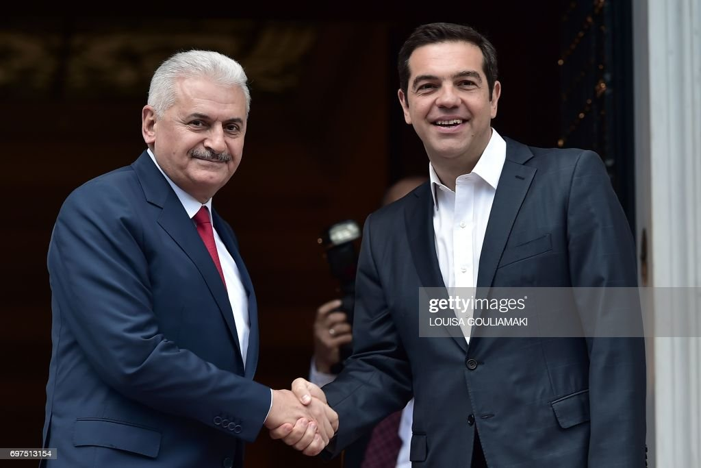 Greek Prime Minister Alexis Tsipras (R) welcomes his Turkish counterpart Binali Yildirim prior to their talks in Athens on June 19, 2017. Yildirim visits Greece to discuss Cyprus ahead of the resumption of UN-backed peace talks on June 28. /