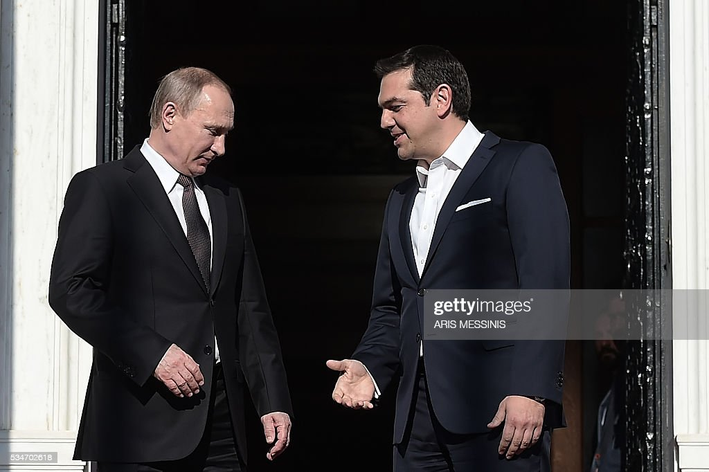 Greek Prime Minister Alexis Tsipras (R) welcomes Russia's President Vladimir Putin before their meeting in Athens on May 27, 2016. Putin is in Greece on a two-day working visit. / AFP / ARIS