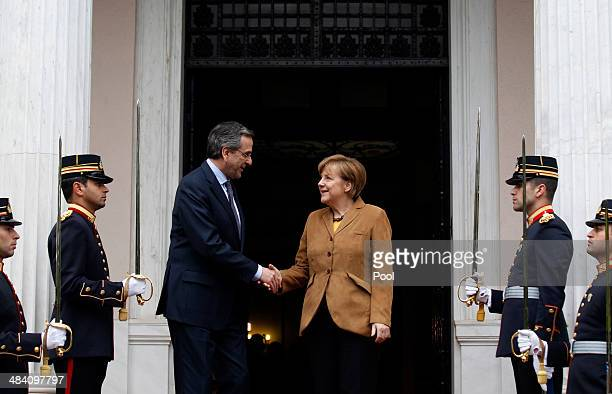 Greek Prime Minister Antonis Samaras greets German Chancellor Angela Merkel on her arrival at the prime minister's office on April 11 2014 in Athens...