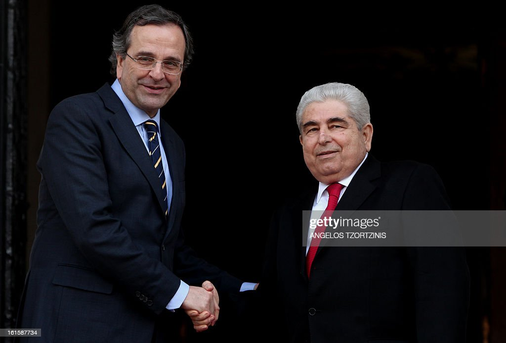Greek Prime Minister Antonis Samaras (L) shakes hands with Cypriot President Demetris Christofias during a meeting in Athens on February 12, 2013. AFP PHOTO / Angelos Tzortzinis
