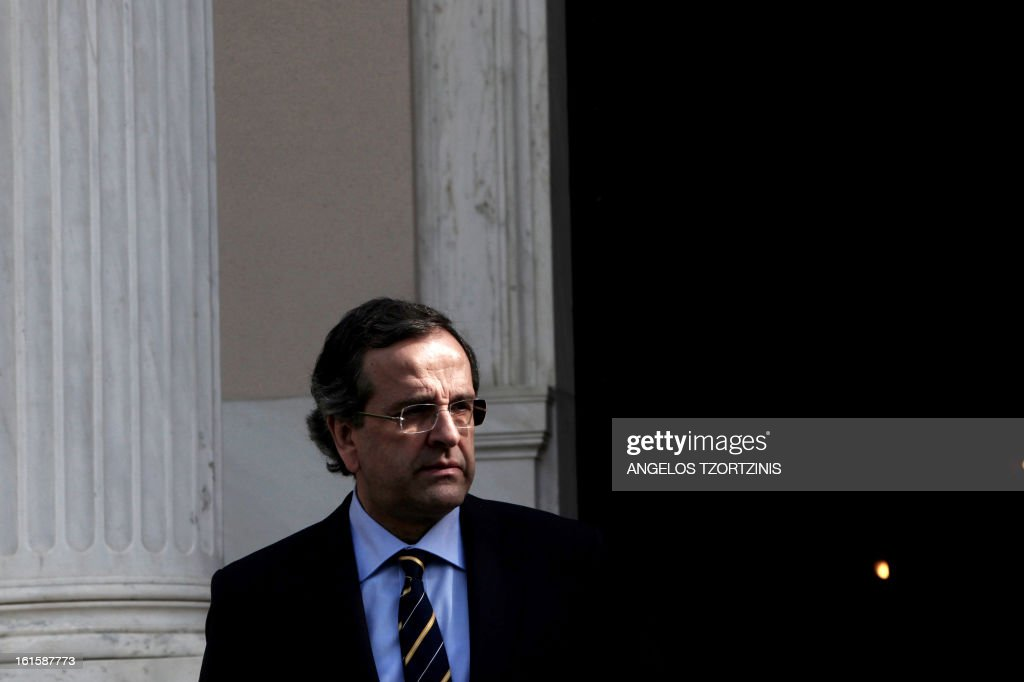 Greek Prime Minister Antonis Samaras waits for Cypriot President ristofias for a meeting in Athens on February 12, 2013. AFP PHOTO / Angelos Tzortzinis