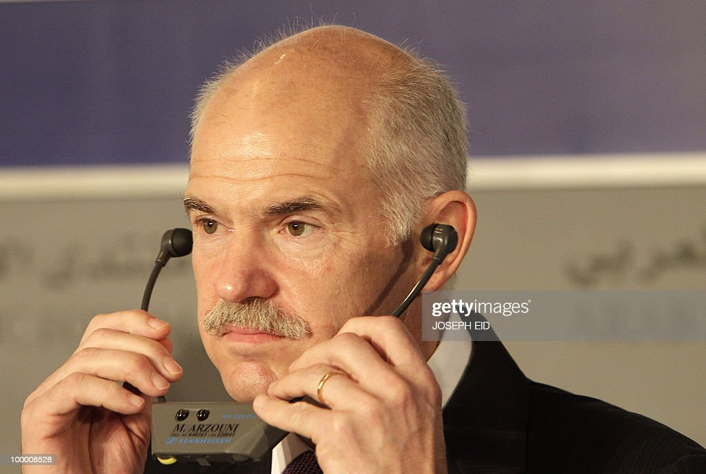 Greek Prime Minister George Papandreou adjusts his headset as he attends the opening session of the Arab Economic Forum in the Lebanese capital Beirut on May 20, 2010. Greece averted default by tapping into a multi-billion-euro EU loan rescue as unions geared up for a new general strike and official figures showed a strong rise in government debt.