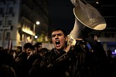 A Greek protester shouts slogans against the government during a demonstration outside the parliament in Athens ahead of a budget vote by lawmakers...