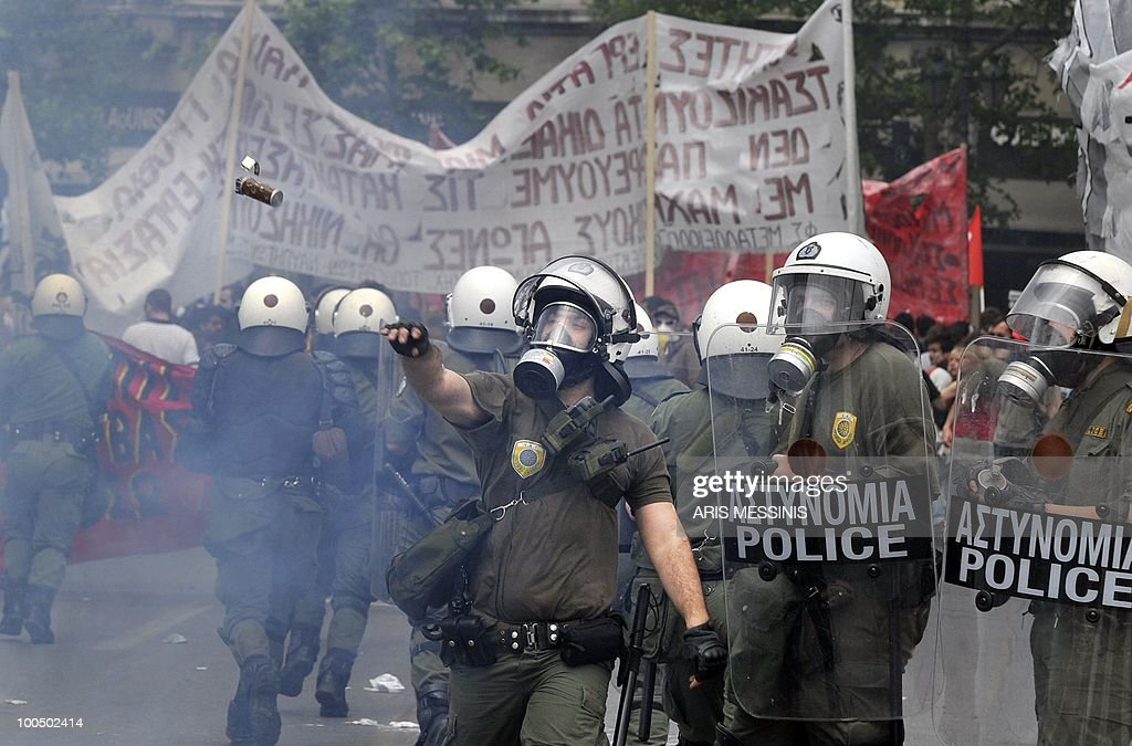 A Greek riot pliceman throws a tear gas granade at protestors during clashes near the parliament in the center of Athens on May 5, 2010. Athens police chiefs mobilized all their forces, including those not on active duty, to restore order on May 5 amid rioting during protests against a government austerity drive. Police were put on a 'general state of alert' to deal with the clashes after three people died in a bank that was firebombed on the margins of the demonstrations.