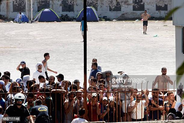 Greek riot police officers stand guard as migrants and refugees wait to be registered at the national stadium on August 12 2015 in Kos Greece Greek...