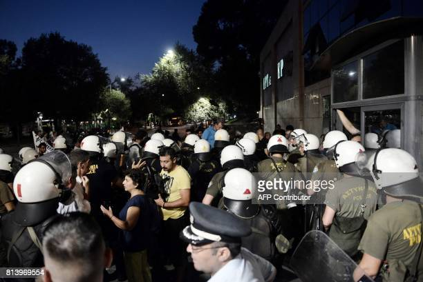 Greek riot police officers stand guard by demonstartors as they protest against the visit of the President of the European Commission JeanClaude...