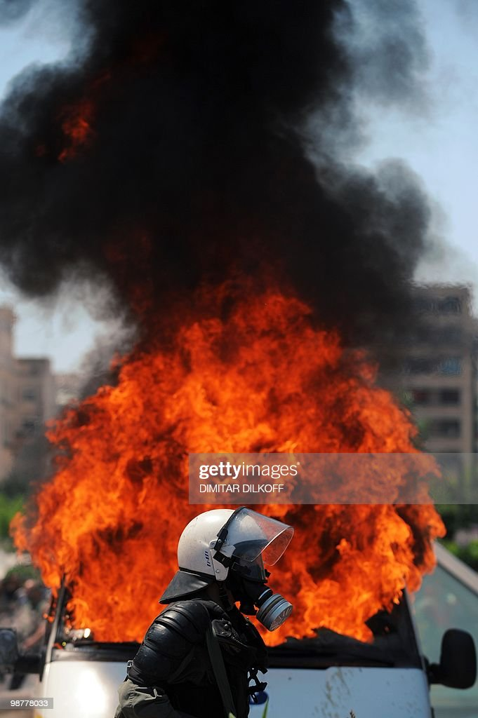 A Greek riot policeman pases by a burning van after a group set fire with a molotov cocktail, during a May day demonstration in Athens on May 1, 2010. Greek police fired tear gas on youths as marchers swarmed through central Athens to protest unprecedented austerity cuts needed for an EU and IMF loans worth as much as 120 billion euros.