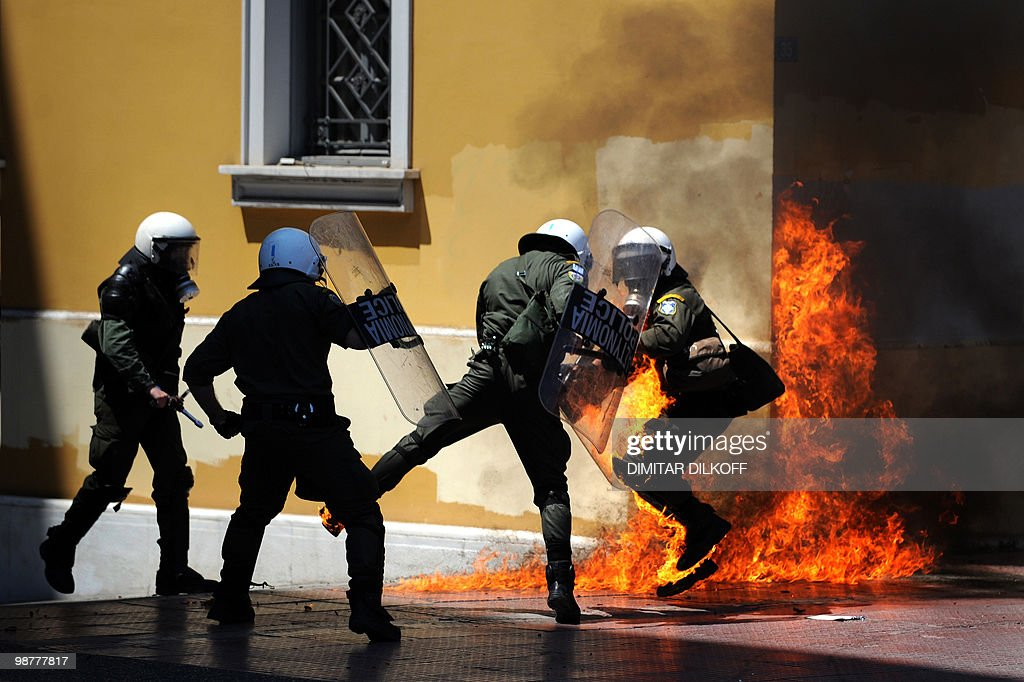 A Greek riot policeman runs away from a fire after a group set fire with a molotov cocktail, during a May day demonstration in Athens on May 1, 2010. Greek police fired tear gas on youths as marchers swarmed through central Athens to protest unprecedented austerity cuts needed for an EU and IMF loans worth as much as 120 billion euros.