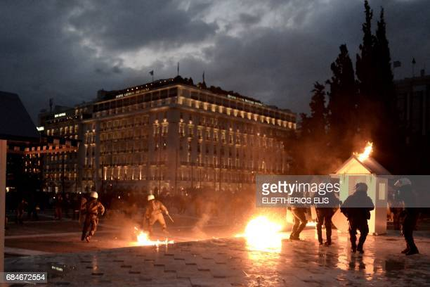 TOPSHOT Greek riot policemen react as protesters throw Molotov cocktails and flares during clashes outside the Greek parliament on May 18 during a...