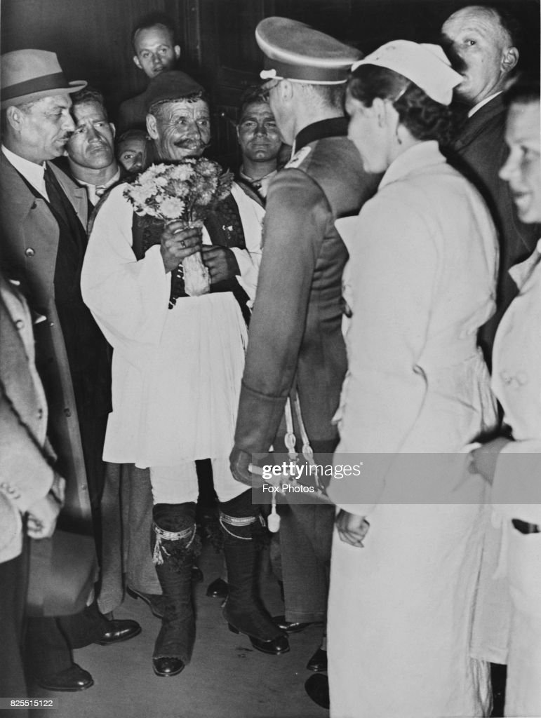 Greek runner Spyridon Louis (1873 - 1940) is greeted upon his arrival in Berlin, Germany, for the Olympic Games, 31st July 1936. The winner of the 1896 Olympic marathon in Athens, he has been selected to light the Olympic Flame with the torch at the opening ceremony the next day.
