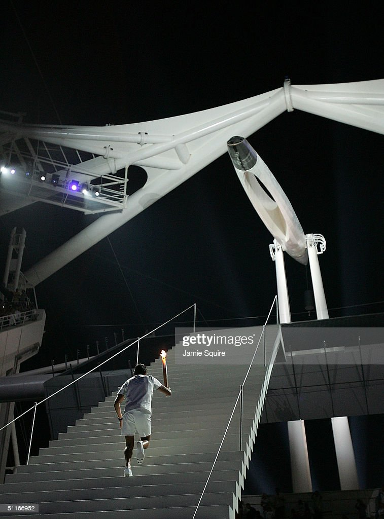 Greek sailor Nicolaos Kakalamanakis runs up stairs with the Olympic torch moments before lighting the Olympic flame during the opening ceremony of the Athens 2004 Summer Olympic Games on August 13, 2004 at the Sports Complex Olympic Stadium in Athens, Greece.