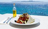 Greek salad and olive oil on sunny sea setup