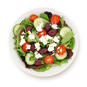 Greek salad with cucumber, cherry tomatos, olives and feta cheese isolated on white (excluding the shadow)