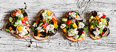 Greek salad style bruschetta on a wooden rustic board, top view. Delicious appetizers for wine or a snack