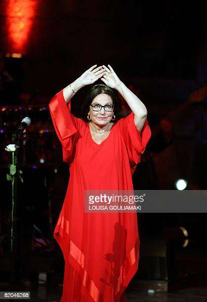 Greek singer Nana Mouskouri greets the public while performing performs in a tribute concert at the ancient Herodus Atticus theatre at the foot of...