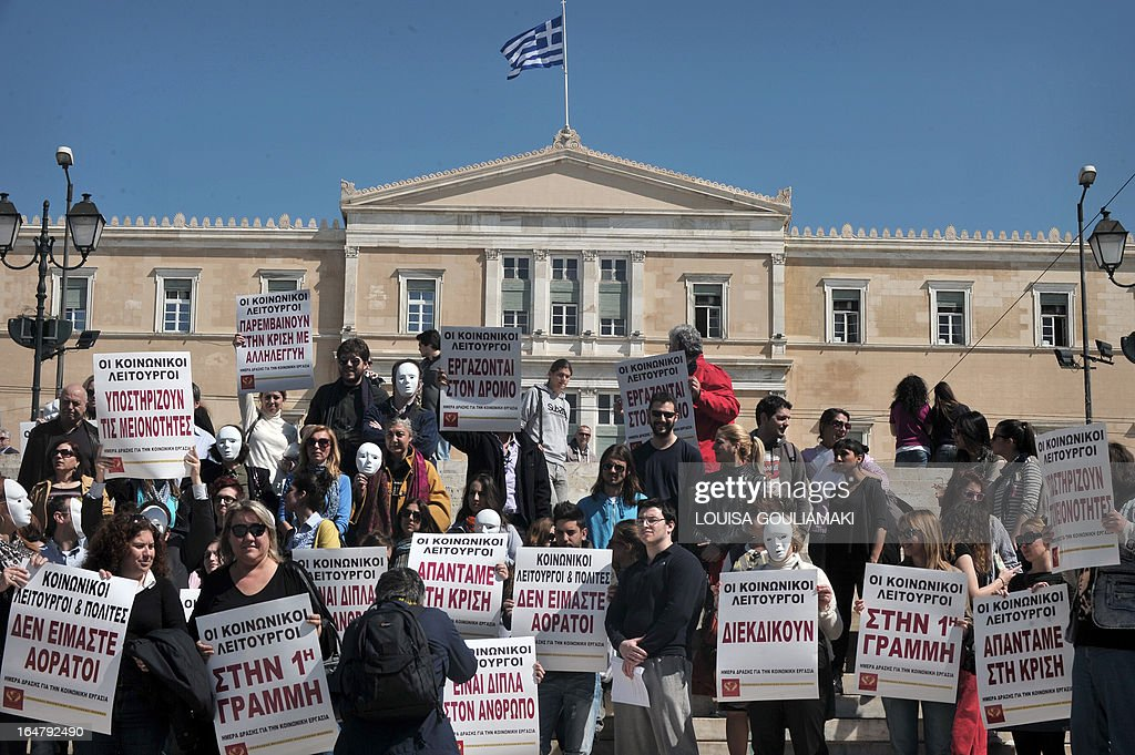 Greek social workers hold placards reading ''we are not invisible', ''we work on the streets'', ''we are helping with solidarity in crisis'' as they protest in front of the Greek parliament against the austerity measures , which affect some of the social programs they work for, on March 28, 2013 in Athens. AFP PHOTO / LOUISA GOULIAMAKI