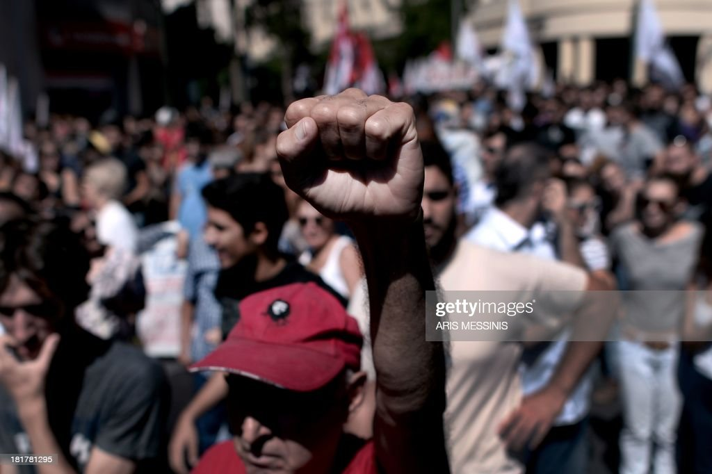 A Greek student raises his fist while taking part in an anti-fascist protest outside the Parliament in Athens on September 25, 2013. Most of the country's mainstream parties called for a large turn-out in the early evening protests, which were sparked by the murder of an anti-fascist musician, allegedly at the hands of a self-confessed neo-Nazi last week.