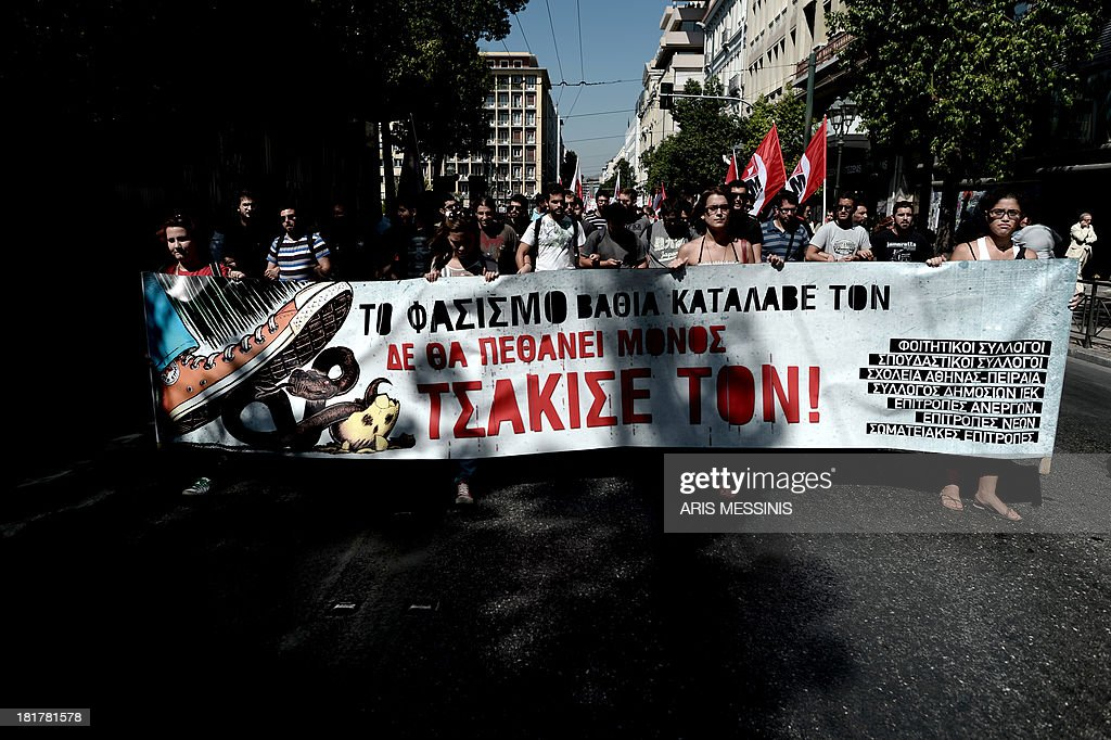 Greek students march behind a banner reading 'Understand Fascismsmash it, it wont die on its own' during a demonstration in Athens on September 25, 2013. Most of the country's mainstream parties called for a large turn-out in the early evening protests, which were sparked by the murder of an anti-fascist musician, allegedly at the hands of a self-confessed neo-Nazi last week. AFP PHOTO / ARIS MESSINIS