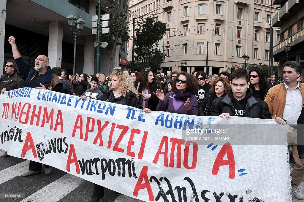 Greek teachers and students march behind a banner reading 'the lesson begins with an A' and 'Agonas (Struggle) Alieggi (Solidarty ), Antistasi (resistance) Anatropi (owerthrow)' during a protest in central Athens on March 2, 2013 against cutbacks in the public education system due to the government's austerity measures. Demonstrators protested on March 2 lack of heat and food in many schools and the overall downgrade of the public education.