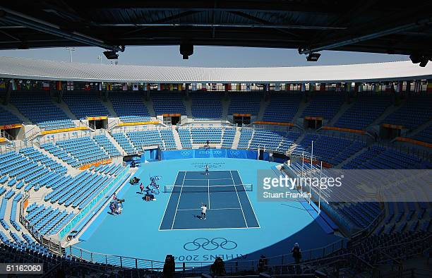 Greek tennis players are pictured on court during practice at the Athens 2004 Summer Olympic Games at the Olympic Sports Complex Tennis Centre on...