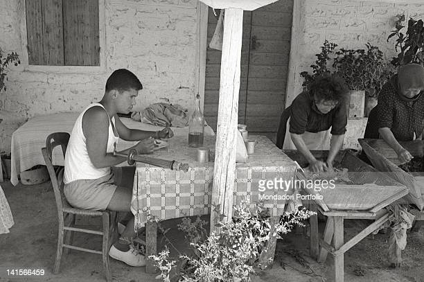 Greek torchbearer eating while two country women are washing clothes Greece 1960