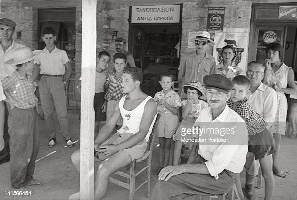 Greek torchbearer posing with a group of people oustide a bar Greece August 1960