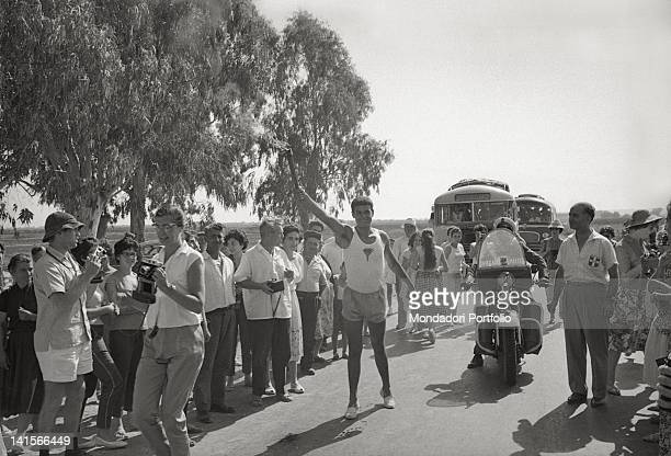 Greek torchbearer posing with the Olympic torch among a group of people Greece August 1960