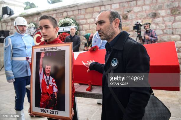 Greek weightlifter Valerios Leonidis stands next to the the coffin of Turkey's legendary triple Olympic goldmedal winning weightlifter Naim...