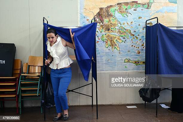 A Greek woman leaves a voting booth at a polling station during a referendum on austerity measures in Athens on July 5 2015 Greece voted in a tightly...