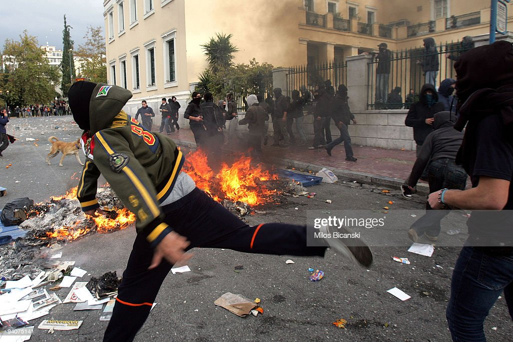 Greek youths clash with riot police during a demonstration commemorating the fatal shooting of 15-year-old Alexandros Grigoropoulos' by police a year ago, on December 6, 2009 in central Athens, Greece. Two police officers will go on trial in the new year for the murder of Grigoropoulos.