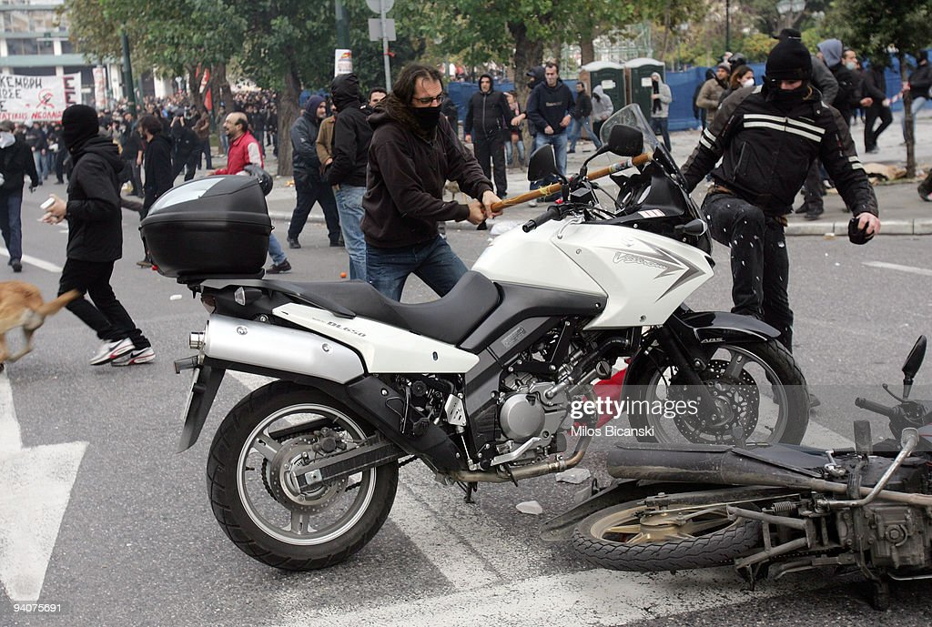 Greek youths destroy police motorbikes during a demonstration commemorating the fatal shooting of 15-year-old Alexandros Grigoropoulos by police a year ago, on December 6, 2009 in central Athens, Greece. Two police officers will go on trial in the new year for the murder of Grigoropoulos.