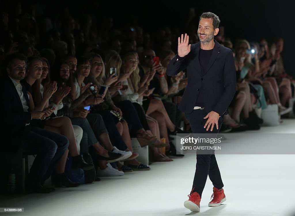Greek-Italian designer Dimitri waves at the end of the presentation of his fashion from the Spring/Summer 2017 collections at the Fashion Week in Berlin on June 30, 2016. / AFP / dpa / Jörg Carstensen / Germany OUT