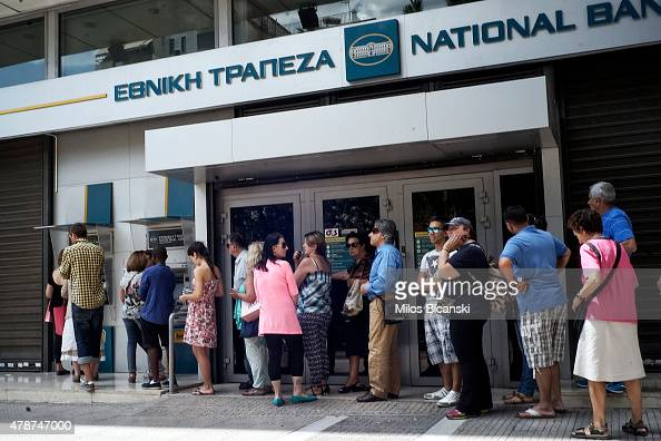 Greeks queue in front of the National Bank to use ATM to withdraw cash as Parliament holds an emergency session for the government's proposed...