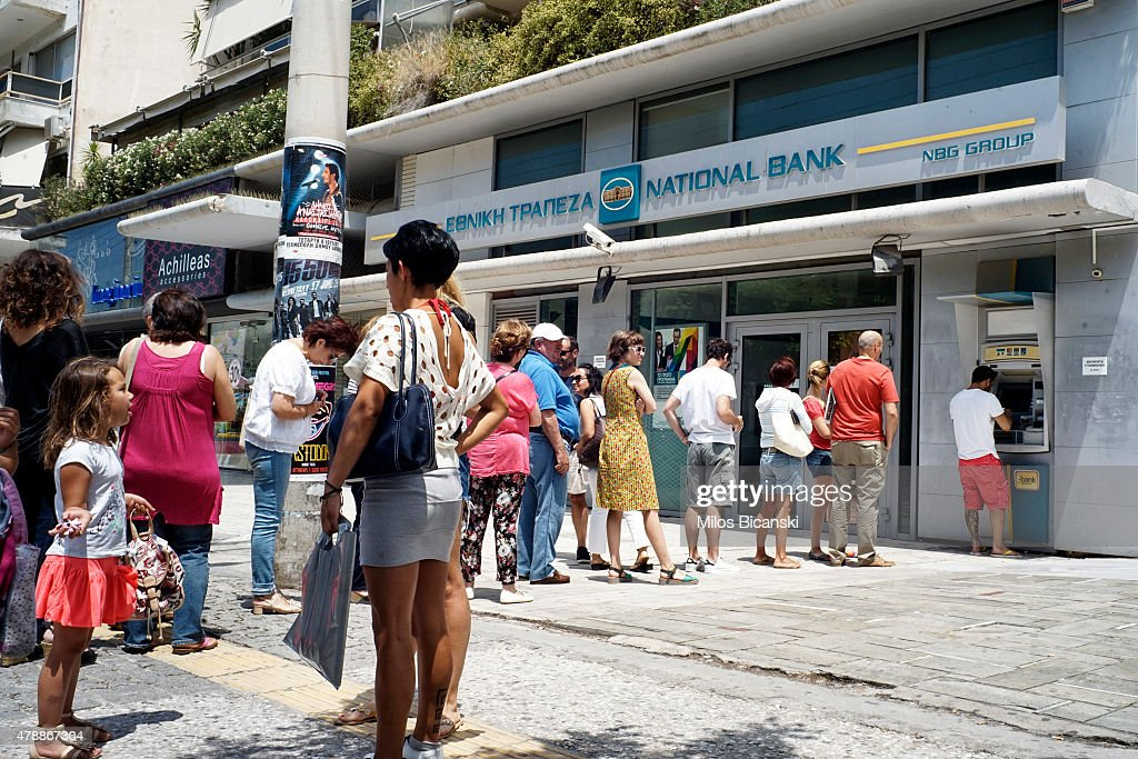 Greeks queue in front of the National Bank to use ATM to withdraw cash on June 28 2015 in Athens Greece Greece is anxiously awaiting a decision by...