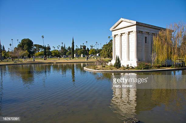 Greek-style mausoleum reflected in pond.