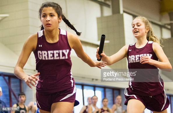 Greely runner Elizabeth Brown takes the baton from teammate Skylar Cooney during the 4 x 200 Meter relay event of the Class B Indoor Track State...