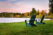 Empty Adirondack Chairs Facing a Lake at Dusk. Beautiful Autumn Colours in Background.