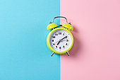 Green classic alarm clock with bells on blue and pink background, top view with copy space