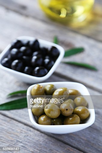 Green and black olives in bowl on grey wooden background : Stock Photo